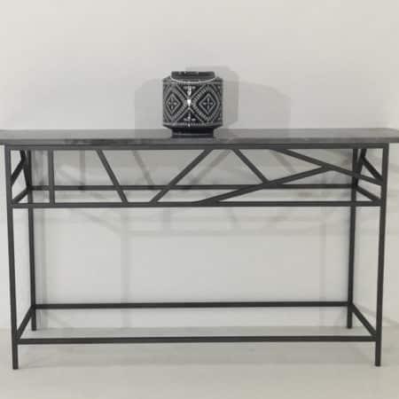 Console design avec plateau en marbre débordant posé sur un piétement en métal plein laqué. Travail artisanal.